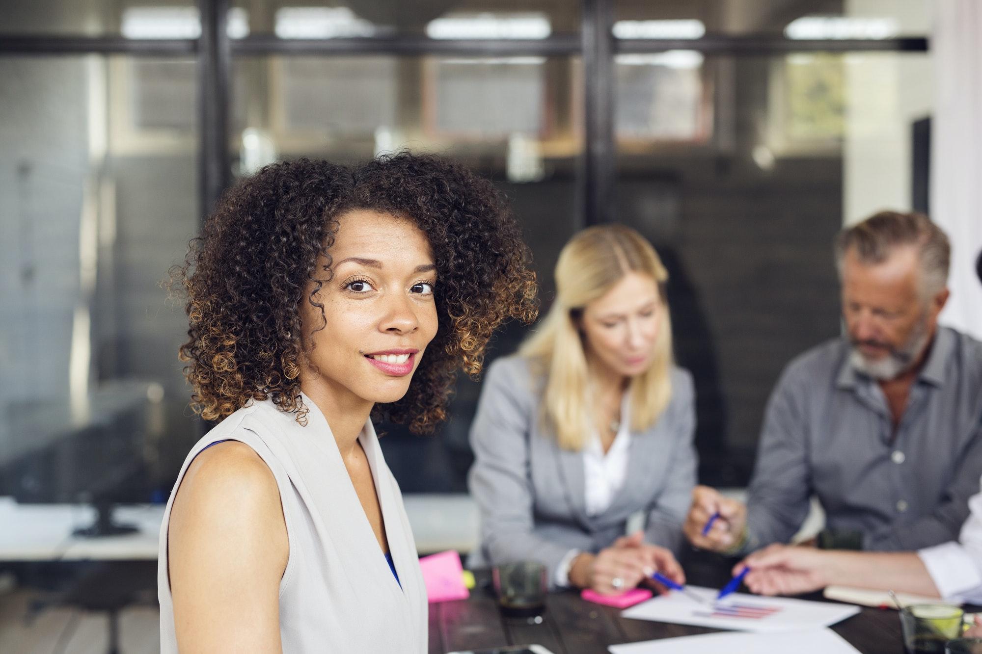 Portrait of brunette woman, Business people working in office in background
